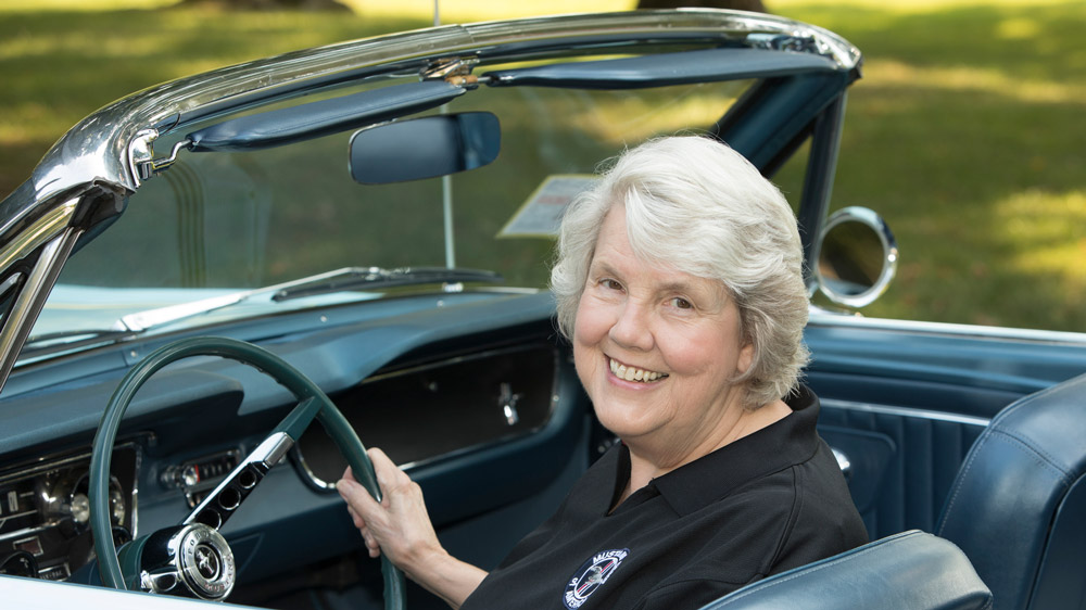 Gail Wise, first person to purchase a Ford Mustang, sits behind the wheel of her car.