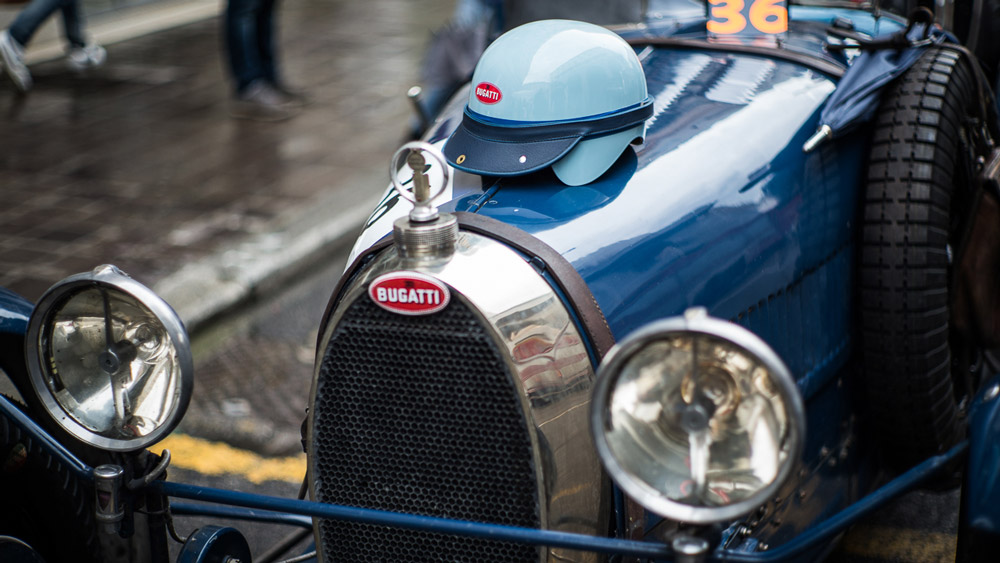 A Pacto race helmet on top of a vintage Bugatti.