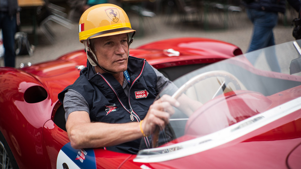 A driver wearing a Pacto helmet behind the wheel of a vintage racecar.