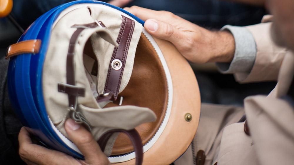 A Pacto race helmet being held.