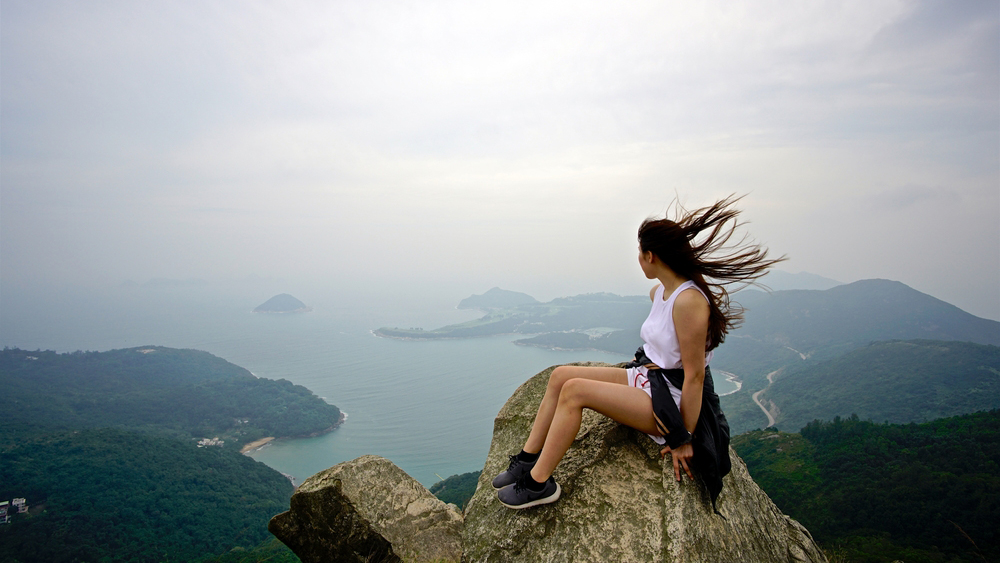 A lady sitting on the peak to enjoy the beautiful view, shot at Junk Bay Peak in Hong Kong on 21 November 2015; Shutterstock ID 717444112