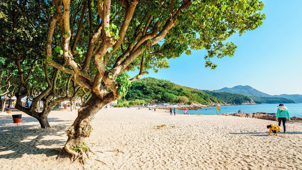 Hung Shing Yeh sandy sea beach with trees on Family Walk trail on sunny day on Lamma Island, Hong Kong; Shutterstock ID 475513441; Notes: Island-hopping in Hong Kong