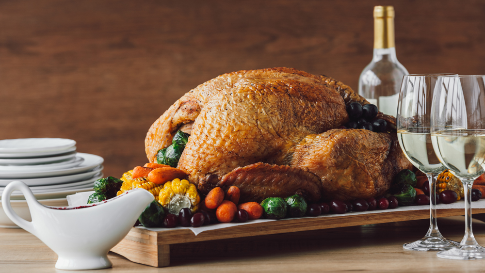 close up view of traditional roasted turkey, vegetables, sauce and glasses of wine for thanksgiving dinner; Shutterstock ID 1182742588; Notes: thxgiv wine