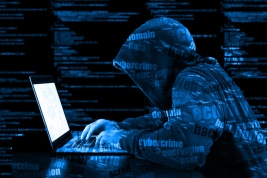 Hacker in a blue hoody standing in front of a code background with binary streams and information security terms cybersecurity concept; Shutterstock ID 547592083; Notes: Hacking on the High Seas