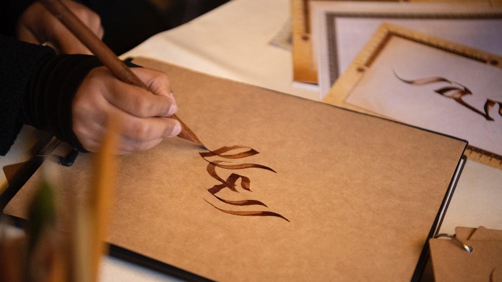 An artisan practices Arabic calligraphy