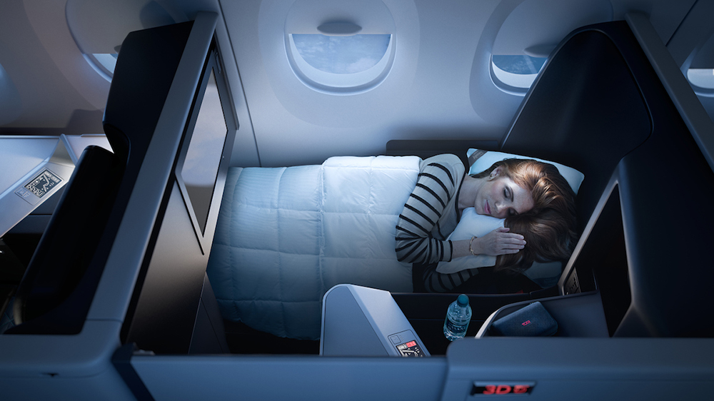 woman sleeping in business class airplane Delta