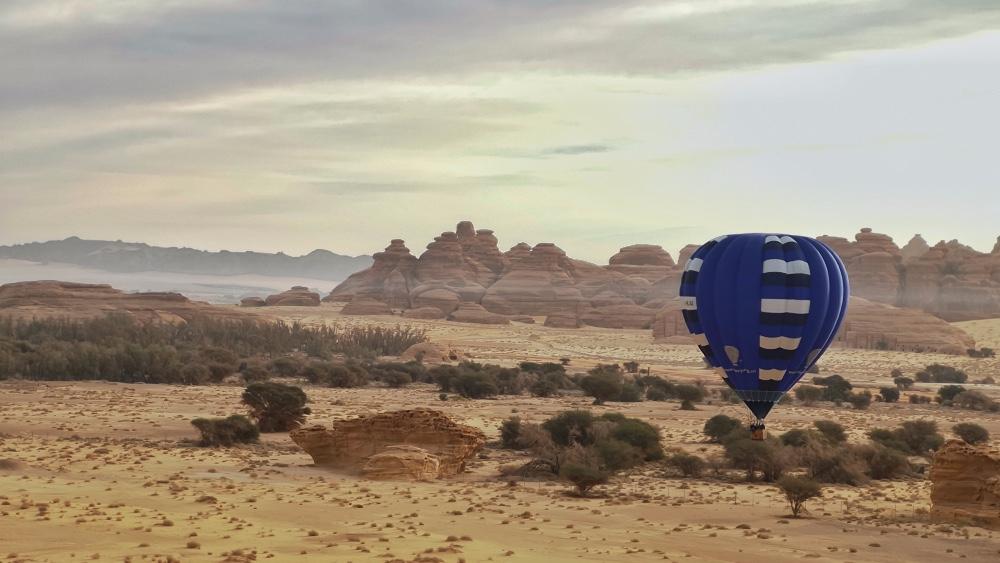 A hot air ballon takes off in the Al-`Ula Valley.