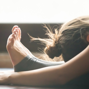 stretching Muse Young woman practicing yoga, sitting in Seated forward bend exercise, paschimottanasana pose, working out, wearing sportswear, grey pants, bra, indoor, home interior background, close up; Shutterstock ID 557789605