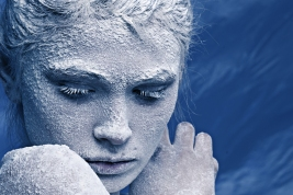 Portrait of a beautiful girl in the frost on his face on a blue ice background; Shutterstock ID 90328729