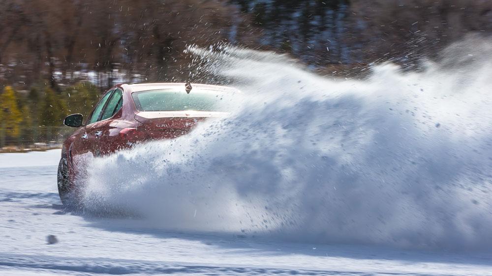 The Genesis G70 sedan being driven in snow.