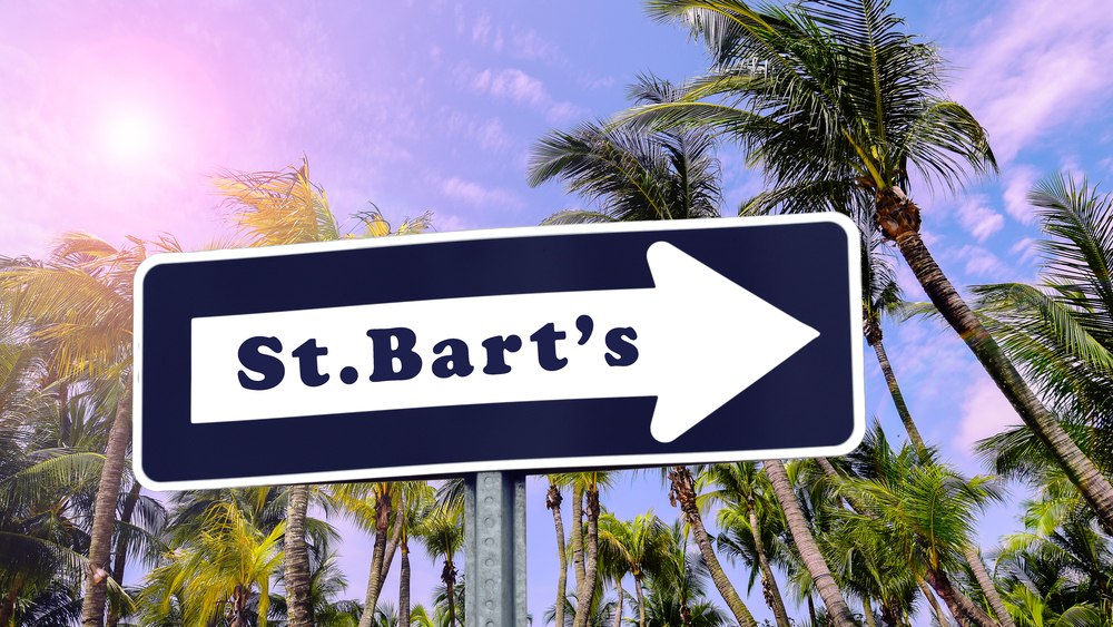 St Bart's arrow sign. Tropical palm trees on the background.; Shutterstock ID 689554249; Notes: Muse_Laid-backStBarts