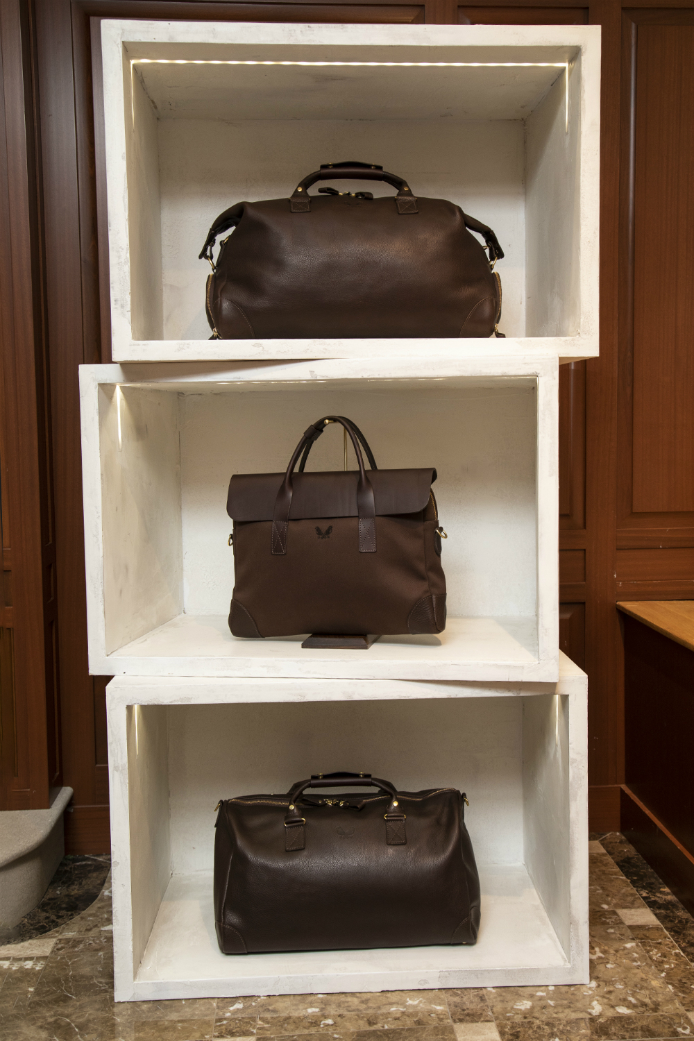Two weekenders and a briefcase from Bennett Winch on display at the Turnbull & Asser townhouse.