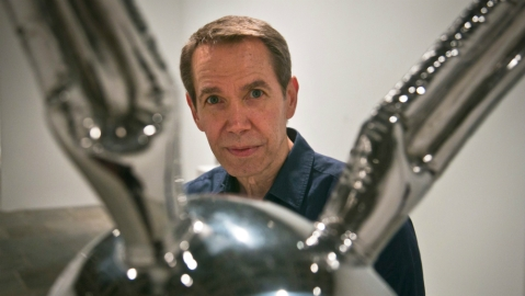 """Jeff Koons poses next to """"Rabbit,"""" one of his oversized toy-like sculptures among works spanning a 30-year career being installed at the Whitney Museum of American Art, in New York."""