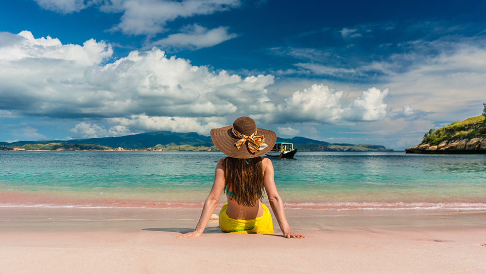 Rear view of a young woman with straw hat looking at an idyllic view while sitting on the sand at Pink Beach in Komodo Island, Indonesia; Shutterstock ID 1029940927; Notes: SE Asia slideshow--Komodo National Park