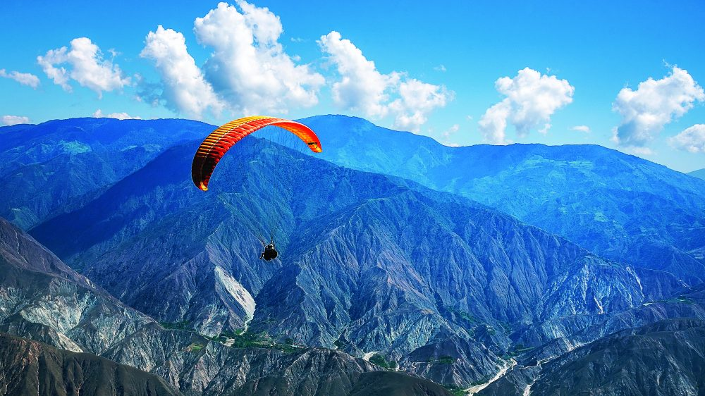 Henry Cookson paraglides down toward a riverbed, where a helicopter awaits to explore Chicamocha Canyon.