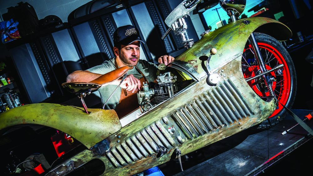 Bueno fine-tuning the carburetor and adding gasoline before awakening the engine of the 1929 Majestic.