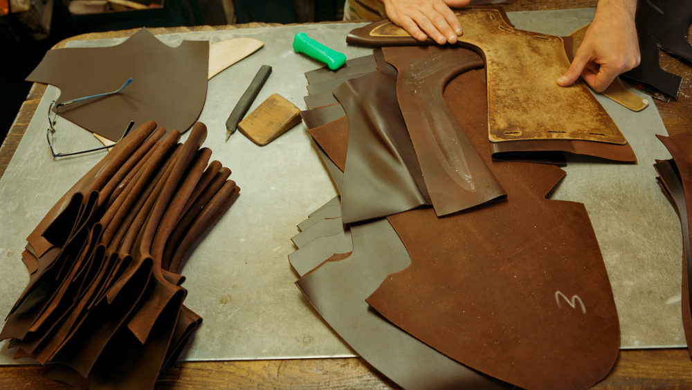 Penelope Chilvers' equestrian-inspired boots, cut from one piece of leather, being prepared for stitching.