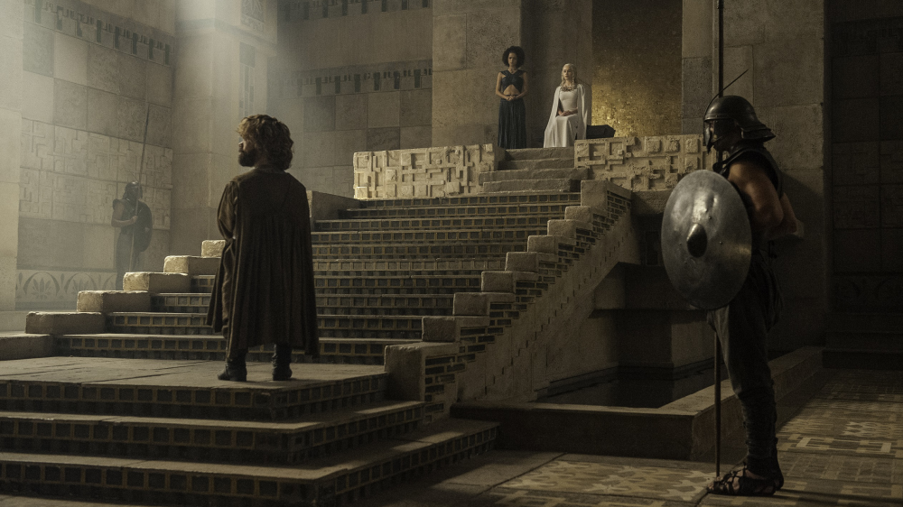 Tyrion Lannister (Peter Dinklage) approaches Missandei (Nathalie Emmanuel) and Daenerys Targaryen (Emilia Clarke) in the Meereen Palace Throne Room.