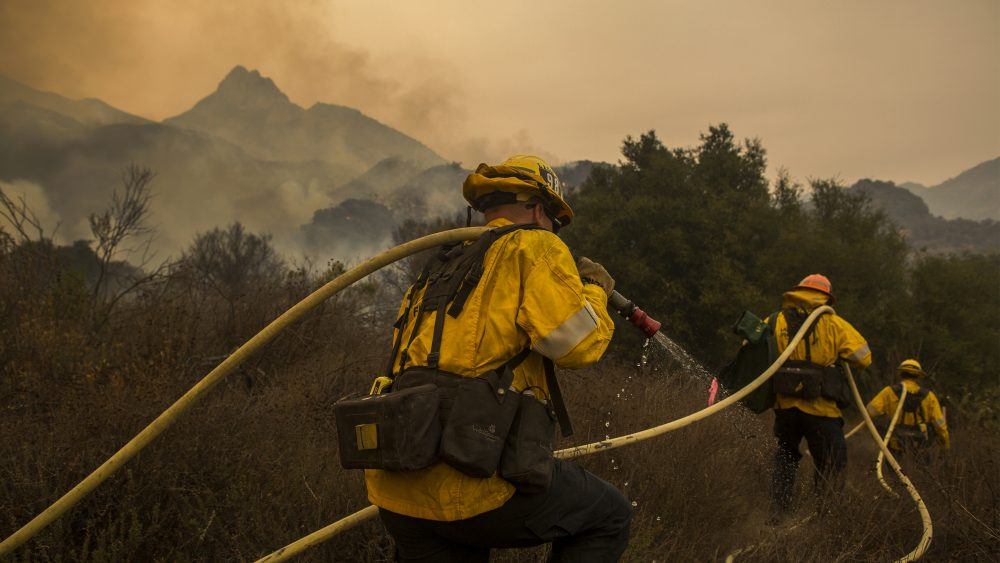Los Angeles County firefighters attack flames approaching the Salvation Army camps in Malibu Creek State Park.