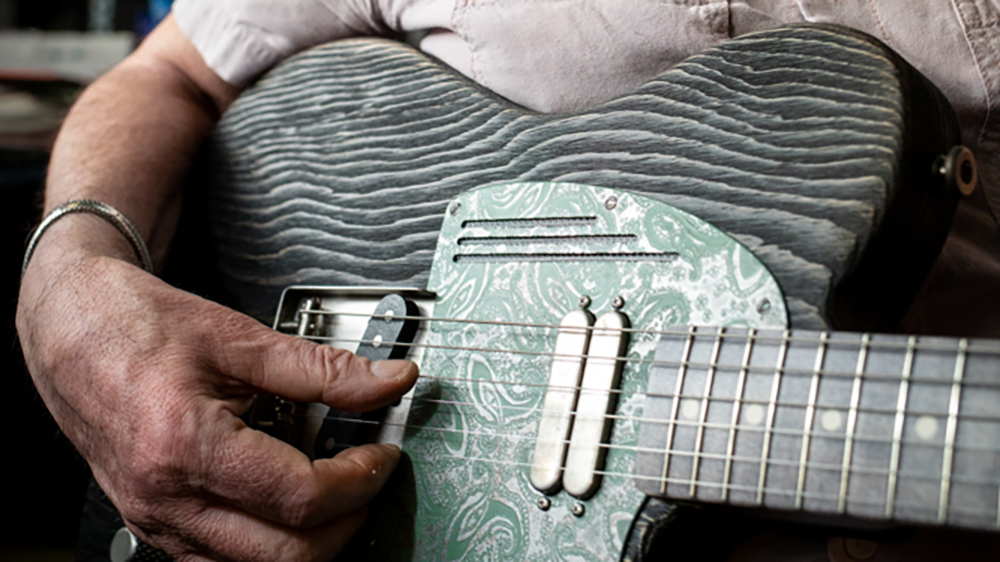 "James Trussart testing the sound of a ""Sage Green Antique Silver Paisley SteelGuardCaster"" guitar in his workshop in Echo Park, Los Angeles."