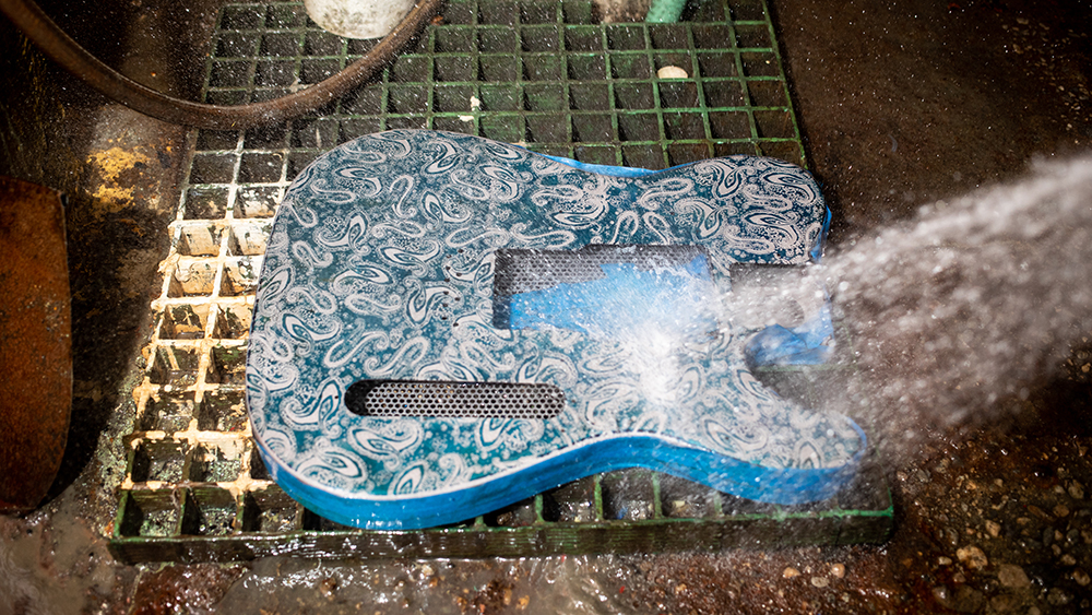 The body of a James Trussart's guitar gets washed after being screen printed and sprayed with the fixer at Trussart's workshop in East Los Angeles.