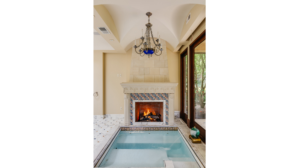 A jacuzzi sits adjacent to a fireplace in the master bedroom.