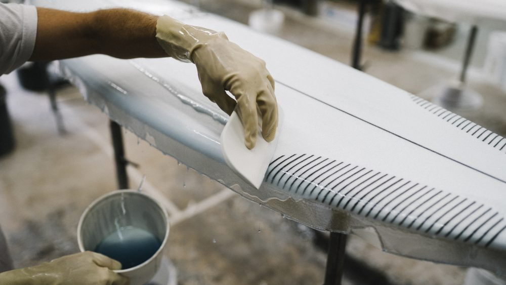 """A layer of resin is applied to the Jon Pyzel surfboard in the """"glassing"""" stage"""
