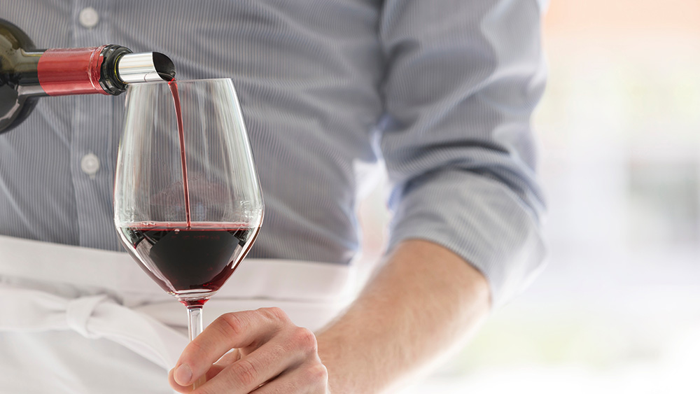 Midsection of waiter pouring red wine in wineglass at restaurant; Shutterstock ID 1413677858; Notes: Robb Report—Waiters (pg 81)