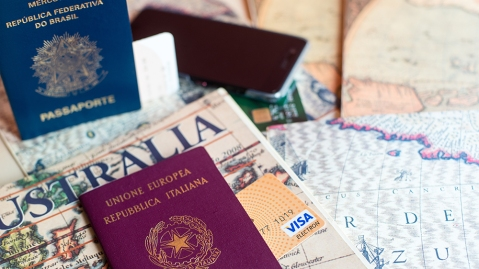 An Italian and brasilian passports and a smartphone over a tourist magazine. Preparations for a trip in South America or Australia. Useful for travel agencies