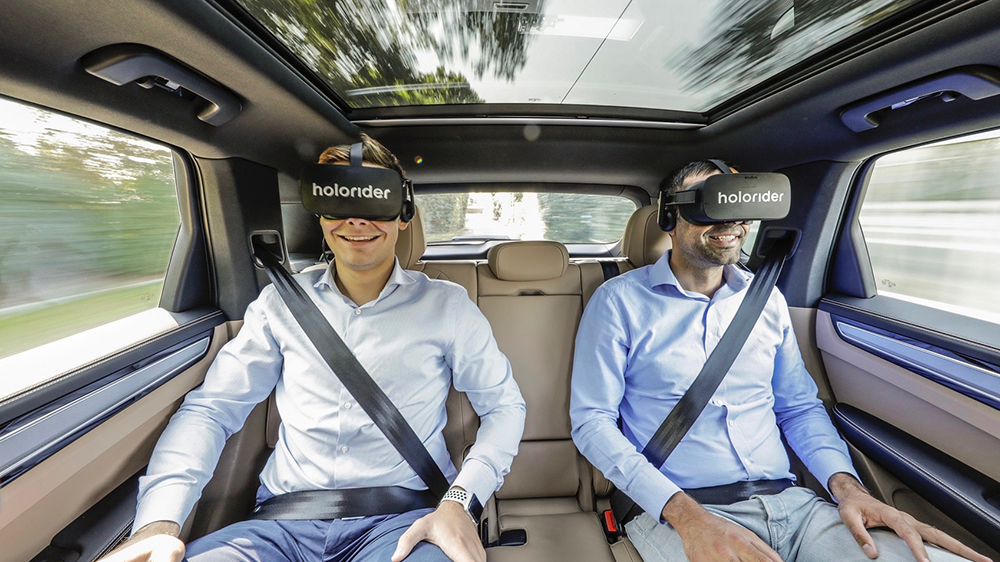 Two passengers wearing Holoride headsets in a Porsche