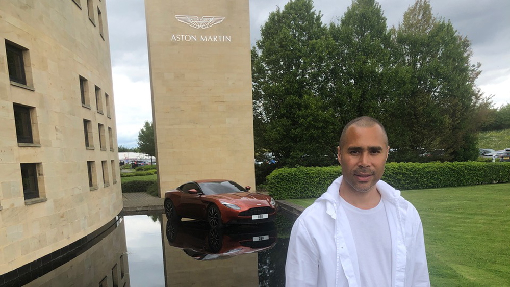 Artist Robi Walters in front of Aston Martin