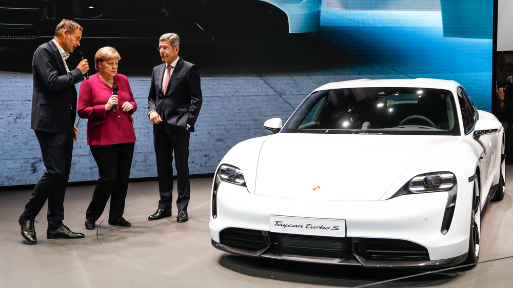 German Chancellor Angela Merkel views the Porsche Taycan Turbo S with Porsche CEO Oliver Blume (left).