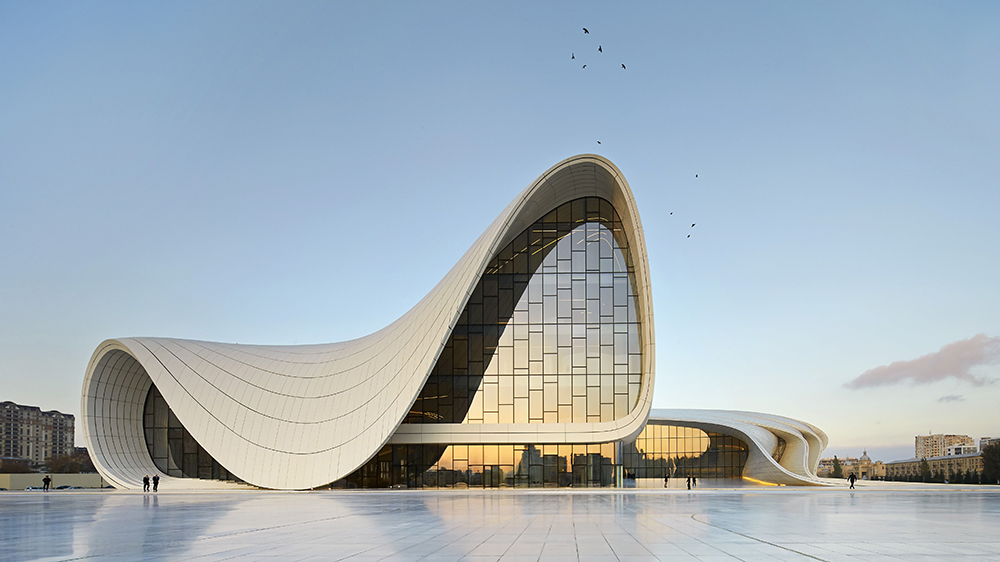 Heydar Aliyev Cultural Center, Baku, Azerbaijan. Architect: Zaha Hadid Architects, 2013. Distant Front Elevation Against Blue Sky. Heydar Aliyev Cultural Center, Baku, Azerbaijan. Architect: Zaha Hadid Architects, 2013.
