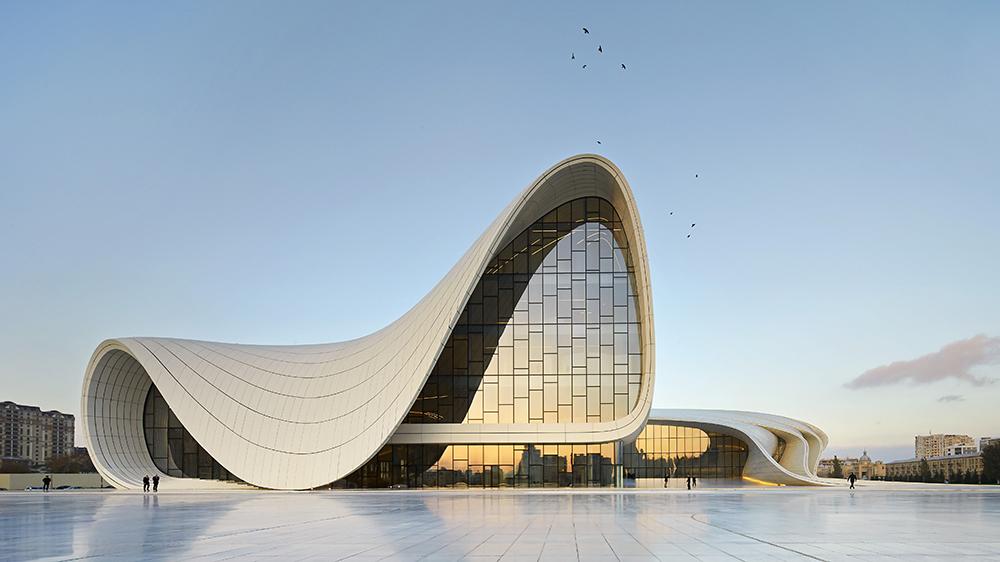 Heydar Aliyev Cultural Center, Baku, Azerbaijan. Architect: Zaha Hadid Architects, 2013. Distant Front Elevation Against Blue Sky. Heydar Aliyev Cultural Center, Baku, Azerbaijan. Architect: Zaha Hadid Architects, 2013.