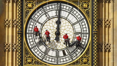 A team of workers cleaning the clock face of Big BenAbseiling workmen on the clockface of St Stephen's Tower, Houses of Parliament, Westminster, London, Britain
