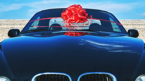 A gift for a loved one. Beautiful black car as a present with a red bow on a sea moor against a blue sky