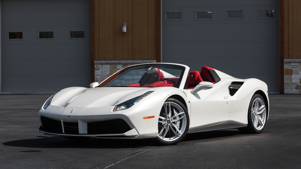 This 2016 Ferrari F488 Spider features a special-order white exterior and a bespoke Rosso Ferrari leather interior.