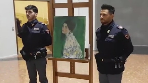 Two police officers guard a painting that some believe is Gustav Klmt's 'Portrait of a Lady'