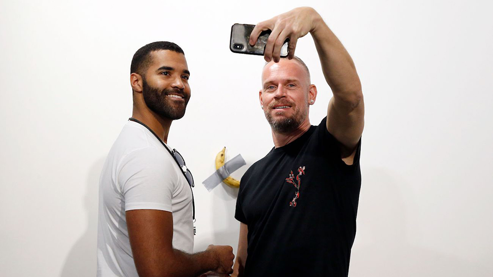 Art patrons take a picture with Italian artist Maurizio Cattelan's piece 'Comedian' (a banana duct taped to the wall) during Art Basel in Miami, Florida, USA, 05 December 2019. Art Basel represents over 250 art galleries onsite at the Miami Beach Convention Center and is considered one of the world's largest art festivals with art events throughout the city.Art Basel, Miami, USA - 05 Dec 2019