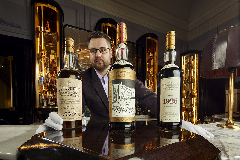 Whiskey Auctioneer Founder Iain McClune with bottles from the Richard Gooding whiskey collection auction.