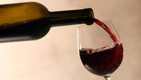 Pouring red wine into glass from bottle against blurred beige background, closeup; Shutterstock ID 1447161149; Notes: Robbreport.com