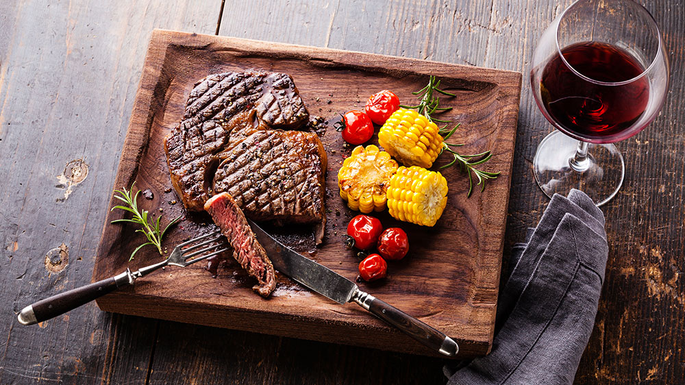 Sliced Medium rare grilled Steak Ribeye Black Angus with corn and cherry tomatoes on serving board block on wooden background; Shutterstock ID 307201292; Notes: Robbreport.com
