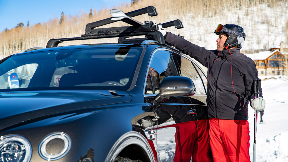 Ski racer Bode Miller next to a Bentley Bentayga.