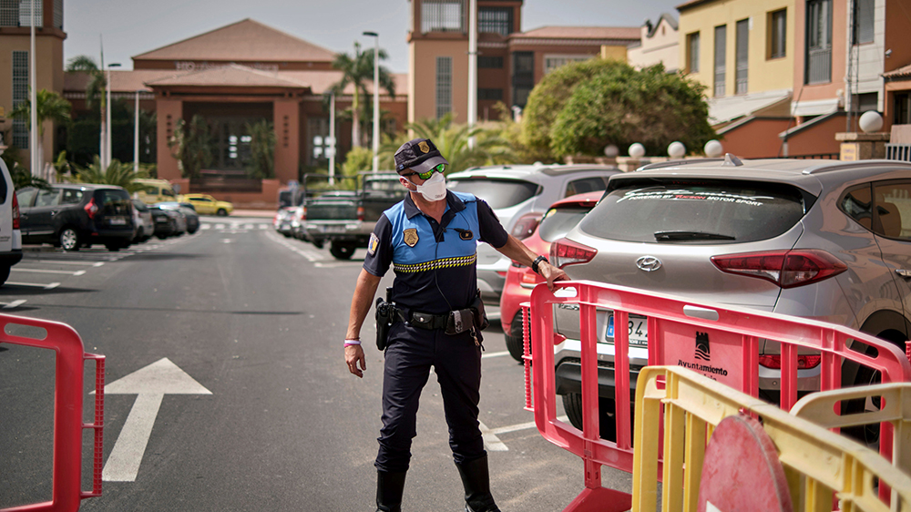 A police officer restricts access to the H10 Costa Adeje Palace resort in Tenerife, Spain