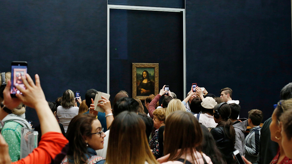 A crowd at the Louvre gathers around Leonardo da Vinci's the 'Mona Lisa'