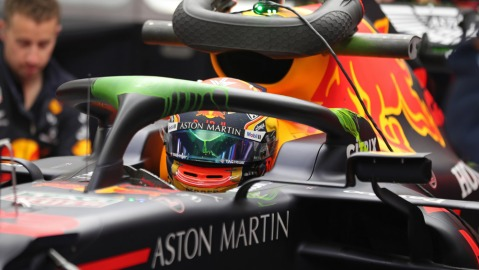 A driver for Aston Martin Red Bull Racing in his race car.