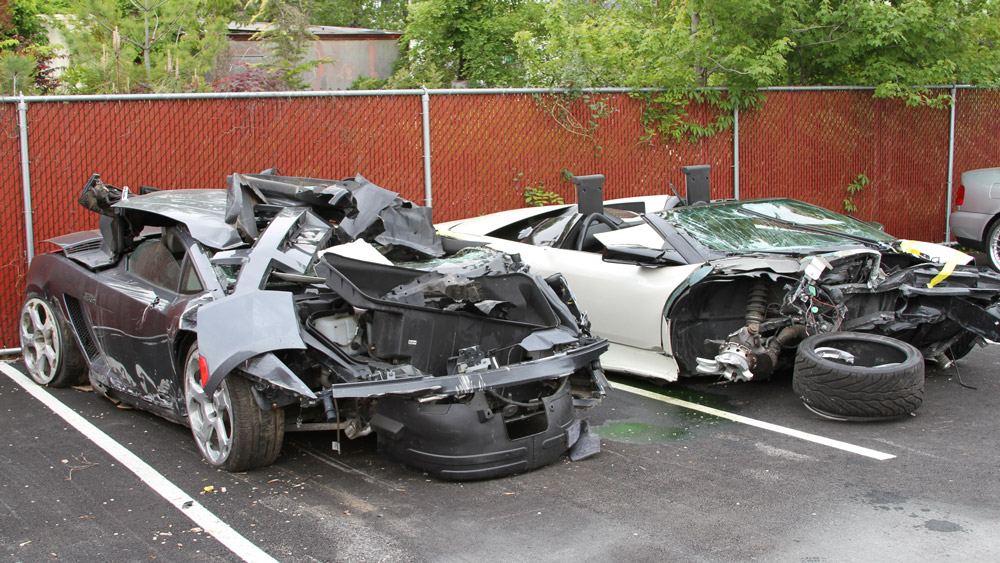 Two wrecked supercars in a parking lot.