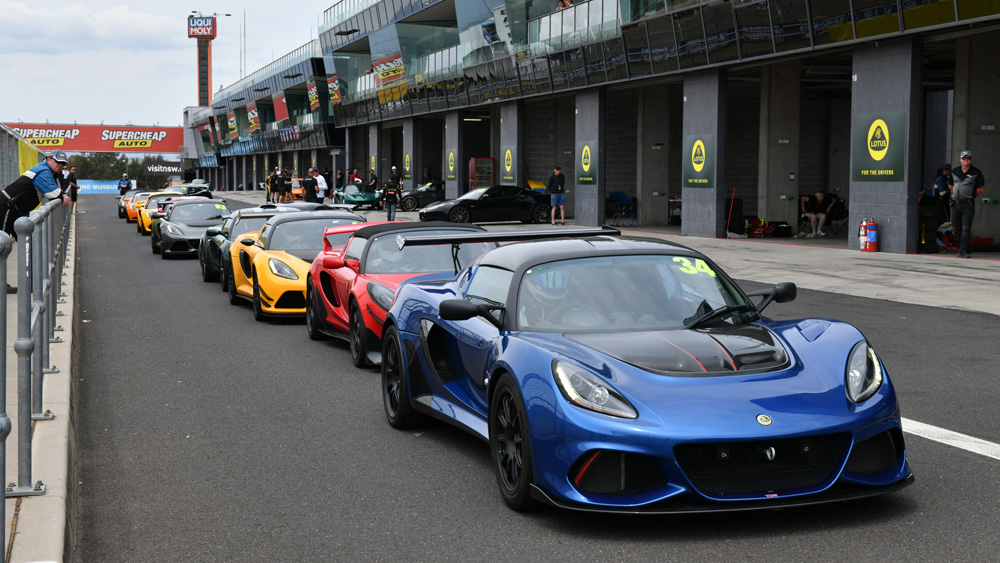 Lotus cars lined up in pit lane at the Bathurst circuit in Australia.
