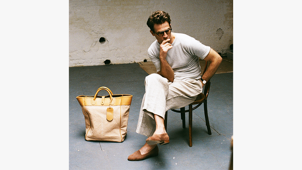 Adret's drop-shoulder knit tee, linen trousers, 'A.M' horn glasses, 'Cary' loafers and 'Graham' tote bag.