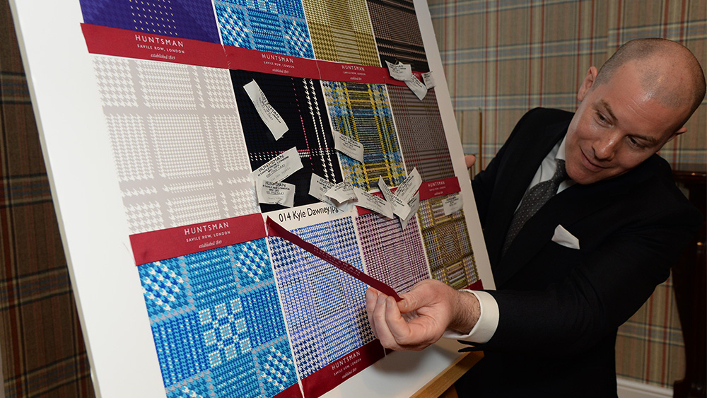 A judge surveying entries in Huntsman's Design Your Own Tweed competition.